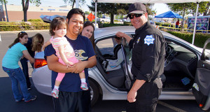 Anthony Ledesma, 21-month-old daughter Cataleya, and wife Bria, are assisted by Fresno Police Officer Beau Burger. (Photo by Cheryl Senn)