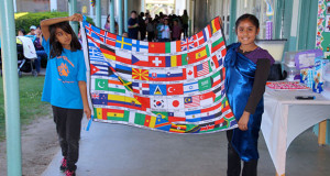 International Fair Parade begins with the presentation of the International Flag by Arlene Chavez and Maria Gaspar.   (Photo by Cheryl Senn)