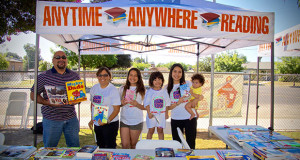 Anytime Anywhere Reading Program premiered at Del Rey Elementary on June 24. L to R - Del Rey principal Pete Munoz, Del Rey Kindergarten teacher Julia Flores, Marissa Flores, Bella Flores and Natalie Flores held by her mother. (Photo by Cheryl Senn)