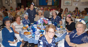 Linda Yost poses with guests at her decorated table. (Photo by Cheryl Senn)