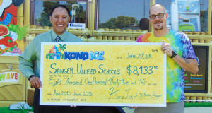 Sanger Unified School District Superintendent Matt Navo is presented with a donation check for $8,133 from the 2015-16 School year, from Kona Ice of Sanger owner Joshua Prieb. (Photo by Benjamin James Ayala/The Sanger Scene).
