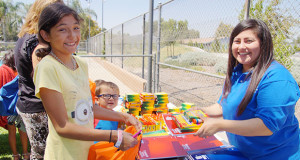 Shaley Klein, a 5th grade student, receives school supplies from Marisol Garcia, at the Sanger Family Resource Center table. (Photo by Cheryl Senn)