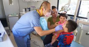 Dr. Paul Hsiao exams Axen Lopez while sister Alexa and mom, Gabriela Jacebo look on. (Photo by Cheryl Senn)