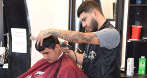 Sanger High graduate, Miguel Medrano, cutting and styling a client's hair. (Photo by Mark Morales/The Sanger Scene)