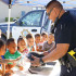 Sanger Police Officer Jose Soto shows students the equipment used by police officers. (Photo by Cheryl Senn)
