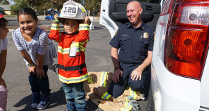 Alonso Angulo, a Wilson pre-school student says he is going to be a firefighter when he grows up and had a great time putting on Sanger Fire Chief Greg Tarasco's helmet. (Photo by Cheryl Senn)