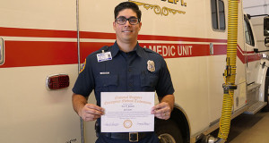 Sanger Firefighter/Paramedic Levi Howlett wearing his new EMS Paramedic badge and displaying his National Registry Emergency Medical Technicians Certificate for his California State Paramedic License. (Photo by Cheryl Senn)