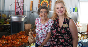 Ninety-year-old Elsbeth Bates experienced the Fresno County Fruit Trail for the first time. Bates is pictured with Sanger District Chamber of Commerce CEO Tammy Wolfe at the Hudson Farms Fruit Stand. (Photo by Cheryl Senn)