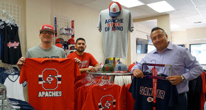 Caleb Bravo, Mike Paredes, and Matthew Graney, pictured L to R,  with some of the Apache Gear available in the store. (Photo by Berenice Vargas)